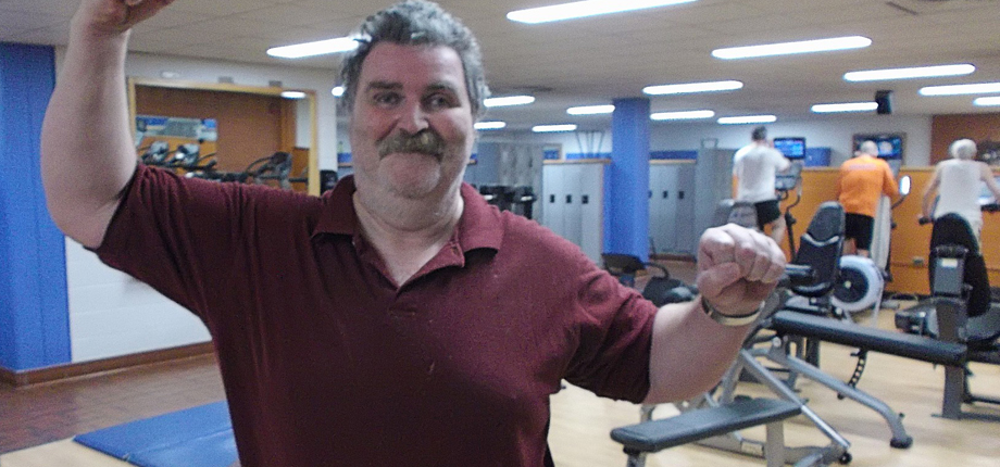 An image of John Black in a YMCA gym raising his arms in celebration after losing 100 pounds