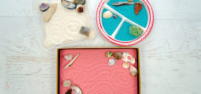 An image of mini zen gardens with pink, white and blue coloured sand decorated with shells