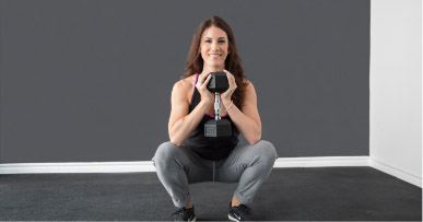 Woman in a squat position holding a dumbbell up to her chest