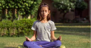 Young girl sits outside in a meditative pose with legs crossed and hands on knees