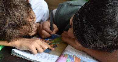 Young kids sit together looking at a book and colouring in it